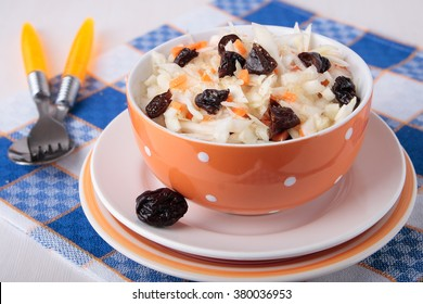 Sweet salad of fresh cabbage with sliced carrot and prunes in a bowl