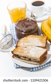 sweet sandwich with chocolate paste and banana for breakfast, vertical top view