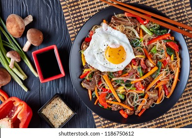 Sweet and savory  korean Japchae: bouncy cellophane noodles with mixed crunchy vegetables: spinach, red bell pepper, onion, carrot, garlic, shiitake mushrooms and beef with fried egg on top, flat lay