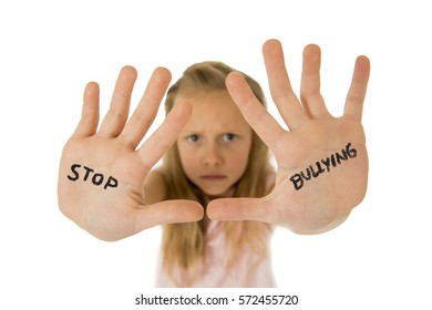 sweet and scared little schoolgirl showing the text stop bullying written in her hands in the concept children bullied and abused in school isolated on white background