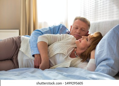 Sweet senior couple cuddling in bed