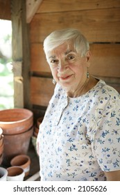 A sweet senior lady gardening in her potting shed.