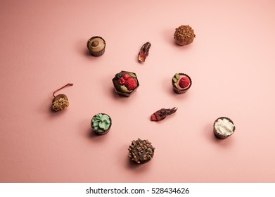 sweet set with colorful chocolate on pink background