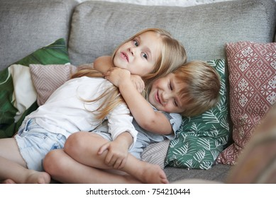 Sweet shot of two adorable little sisters hugging on sofa in living room: baby girl with short hair embracing her elder sister tight, holding hands around her neck, surrounded with decorative pilows
