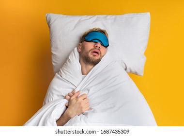 Sweet sleep in comfortable bed. Guy sleeps in mask, top view, free space