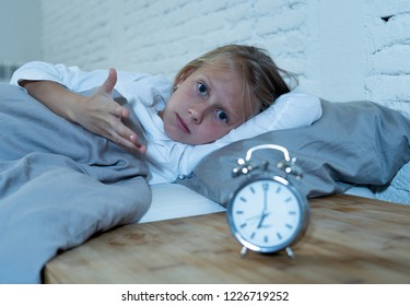 Sweet sleepless little girl lying sad in bed looking at alarm clock having to wake up but feeling tired sleepless in Troubles staying asleep Night Terrors Sleep disorder and Children Insomnia concept.