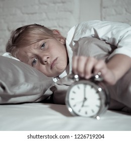 Sweet sleepless little girl stressed sad and angry in bed looking at alarm clock having to wake up but feeling sleepless in Troubles staying asleep Sleep disorder and Children Insomnia concept.