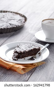 Sweet slice of brownie and whole cake in background. Homemade dessert decorated with sugar powder served with espresso.
