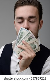the sweet smell of money. a young man sniffing the money and dreams