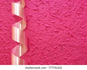 Sweet soft pink ribbon and bright pink rough paper background.