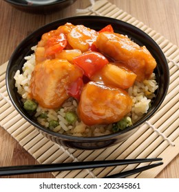 Sweet and sour chicken Cantonese style with egg fried rice in a lacquer bowl with chopsticks