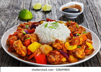 Sweet and Sour fried pork chunks with vegetables and rice, sprinkled with green onion on white dish on dark wooden background with soy sauce and slices of lime, view from above, close-up