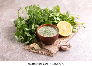 Sweet and sour green homemade sauce with cilantro, lemon and garlic on the burlap napkin background. Horizontal view. Copyspace