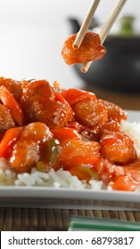 sweet and sour pork on rice being eaton with chopsticks