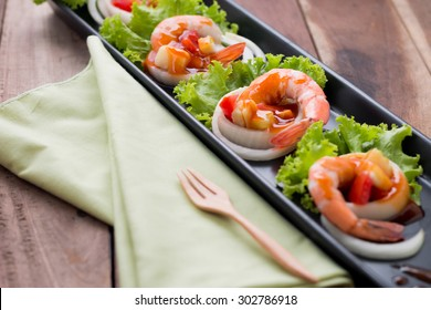 sweet and sour shrimp, prawn cocktail on long square dish and wooden table