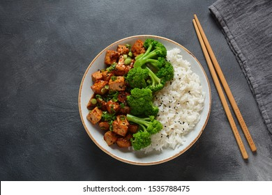 Sweet, spicy , crispy and fried Tofu in teriyaki sauce served in  a  bowl with broccoli, sesame seeds and rice. Healthy vegan food, gluten-free