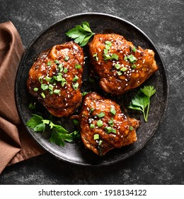 Sweet and spicy honey grilled chicken thighs on plate over dark stone background. Tasty food in asian style. Top view, flat lay, close up
