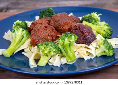 sweet and spicy meat balls meal over pasta with broccoli