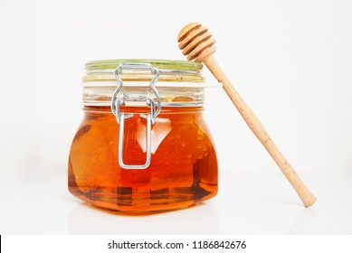 Sweet sticky honey jar with comb isolated on white
