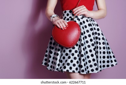 Sweet stylish young woman wearing polka dot dress with red heart lovely bag. Fashion concept