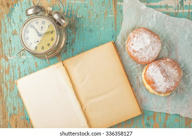 Sweet sugary donuts, old book and vintage alarm clock on rustic wooden kitchen table, top view of tasty bakery doughnuts in vintage retro toned overhead shot