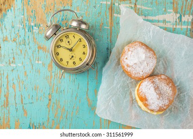 Sweet sugary donuts and vintage alarm clock on rustic wooden kitchen table, top view of tasty bakery doughnuts in vintage retro toned overhead shot