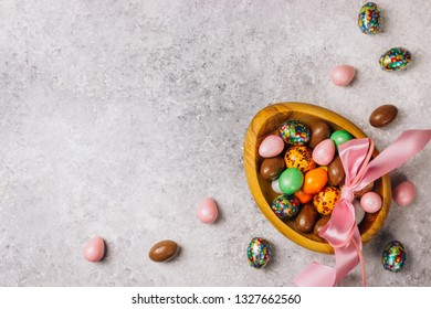 Sweet Sugary Easter Candy eggs in a wooden bowl on light gray backround. Top view