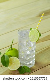Sweet summer limeade, fresh limes cocktail with juice and mint on a wooden table.