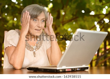 13f9adb7 Sweet surprised older woman sitting at a table at home on the veranda