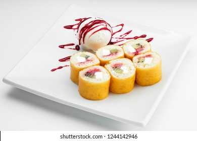 Sweet sushi roll dessert  with fruits and icecream on a white plate
