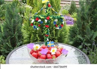 Sweet Swedish strawberries for Midsummer,  maypole in background