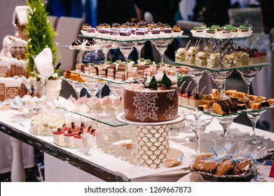 Sweet table. A plates of cakes and muffins with cream with berries. Table with sweets, candy, buffet. Dessert table for a party goodies for the wedding. Close up. candy bar. Decorated delicious.