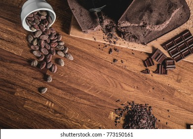Sweet Table Top View arrangement of Cocoa beans, nibs and Chocolate bars on wooden surface.