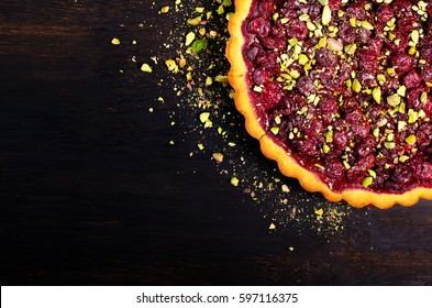Sweet tart with raspberries, cherries, red currants with pistachios, powdered sugar on dark wooden background. Copyspace. top view.