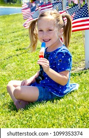 The sweet taste of freedom! A cute little girl eats a red white and blue Popsicle, as she sits on a hill surrounded by american flags