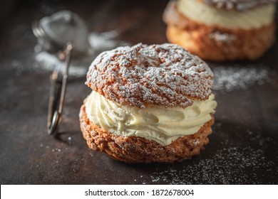 Sweet and tasty cream puffs with powdered sugar on baking tray