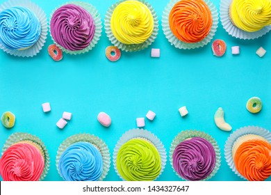 Sweet tasty cupcakes with candies on color background