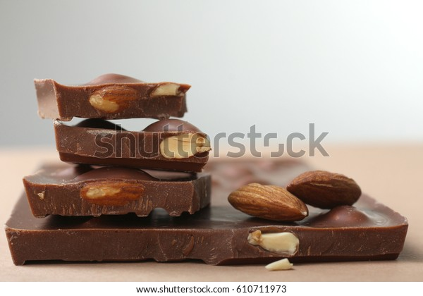 Sweet and tasty milk chocolate with almonds on a brown table on a gray background