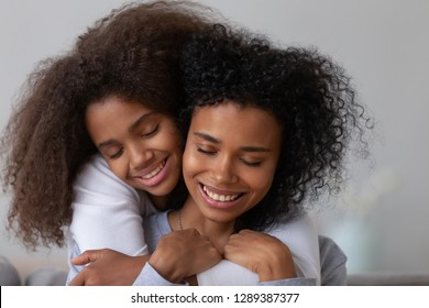 Sweet teenage daughter hug young African American mom from behind showing love and care, tender teen girl embrace mother or nanny, parent and child have close intimate moment together