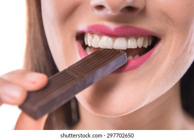 Sweet temptation. Beautiful woman tasting  piece of chocolate over white background. Close-up.