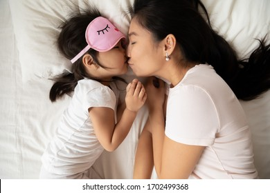 Sweet tender moment of mom kiss child close up top view. Loving mum puts child to healthy day night sleep, asian family lying in bed, kid girl wears pink sleeping eyemask. Love health care concept