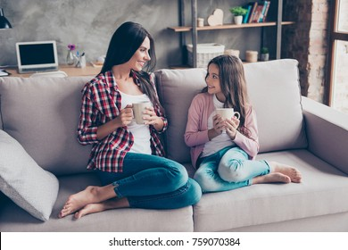 It is so sweet time! Concept of being the best friends with a mother. Pretty young smiling cheerful mum and her lovely daughter are sitting on a couch drinking cacao and sharing secrets