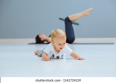 Sweet toddler baby boy crawling on the floor while his mother exercising with pilates ring lying on grey yoga mat on background. Fitness, happy maternity yoga with children concept.
