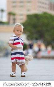Sweet toddler baby boy, playing with teddy bear in the city on a quiet evening