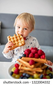 Sweet toddler birthday boy, eating belgian waffle with raspberries, blueberries, cocnut and chocolate at home