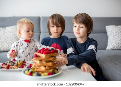 Sweet toddler birthday boy and his brothers, eating belgian waffle with raspberries, blueberries, cocnut and chocolate for breakfast at home