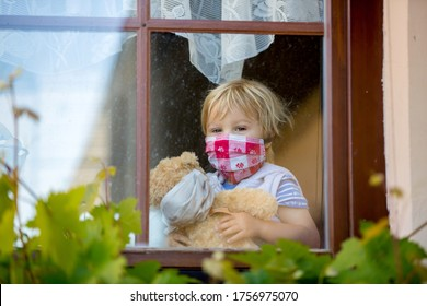 Sweet toddler boy, wearing medical mask, hugging teddy bear, also with mask, looking sadly out of the window, during coronavirus pandemic isolation
