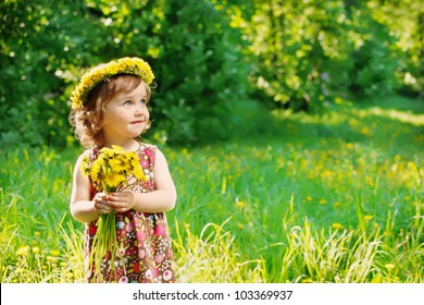 Sweet toddler girl with floral head wreath on and flowers bunch in hands