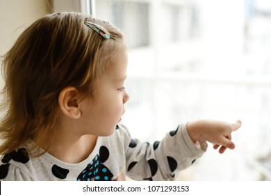sweet toddler girl looking in the window