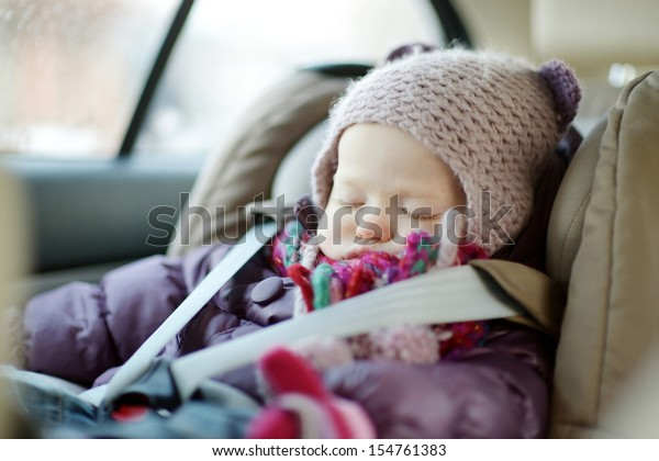 Sweet toddler girl sleeping peacefully in a car seat at winter